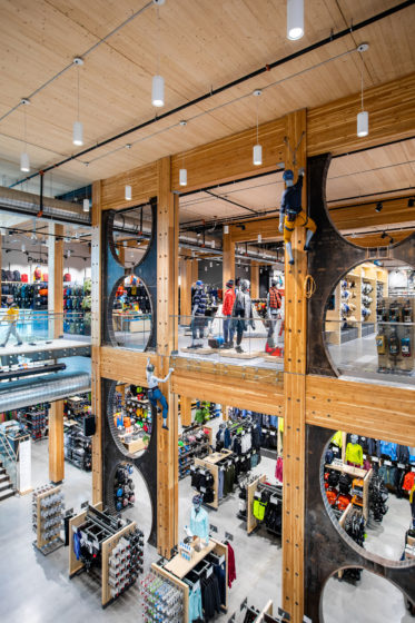 Mannequins climb timber beams at MEC's new flagship in Vancouver