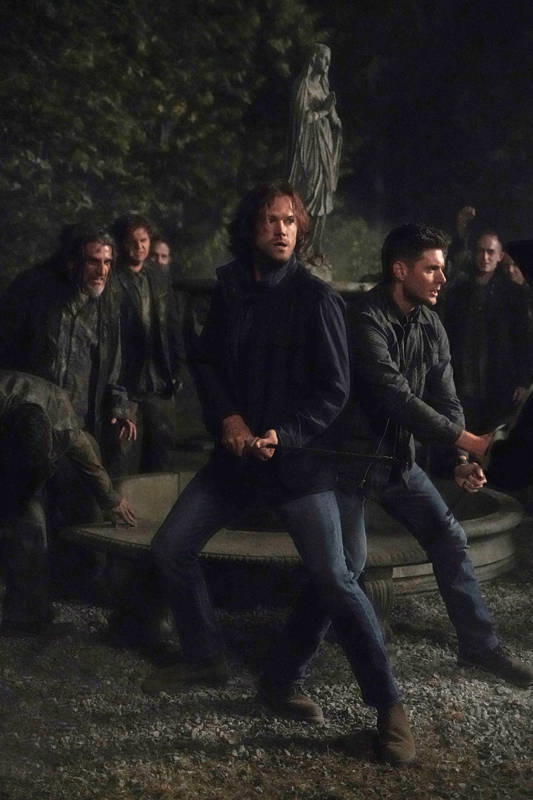 A scene from Supernatural where Sam and Dean battle evil in a cemetery